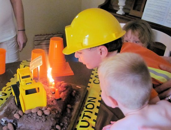 Blowing out candles on Construction Cake