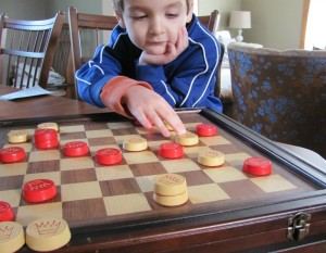 Five year old playing checkers