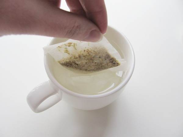 Use your fingers to drop tea bag into water